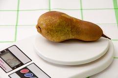 Pera su una scala digitale della cucina bianca Fotografia Stock