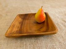 Pera sul piatto di legno Fotografia Stock Libera da Diritti