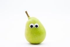 Pera verde con gli occhi googly su fondo bianco Immagini Stock Libere da Diritti