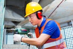 Perçage asiatique de travailleur dans le mur de chantier de construction Image stock