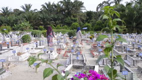 PERAK, MALAYSIA, Circa July 2015 - Two muslim women looking for their relative's grave at a big Muslim graveyard in the town of Ip stock video footage