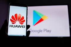 A man holds an android-smartphone. PERAK, MALAYSIA - MAY 24, 2019: A man holds an android-smartphone that shows the Huawei logo in front of the google play store royalty free stock images