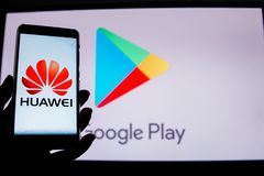 A man holds an android-smartphone. PERAK, MALAYSIA - MAY 24, 2019: A man holds an android-smartphone that shows the Huawei logo in front of the google play store stock photo