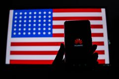 A man holds an android-smartphone. PERAK, MALAYSIA - MAY 24, 2019: A man holds an android-smartphone that shows the Huawei logo in front of the USA flag. Google stock image