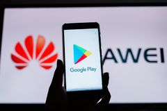 A man holds an android-smartphone. PERAK, MALAYSIA - MAY 24, 2019: A man holds an android-smartphone that shows the logo for the google play store in front of stock image