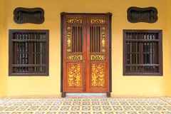 Peranakan Style Home Exterior in Penang. Peranakan typical style windows and ornate entrance doors an floor tiles in Penang Malaysia Royalty Free Stock Image