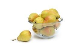 Peras amarillas en el plato de cristal con una pera a un lado Imagen de archivo libre de regalías