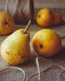 Peras amarillas en una tabla de cocina con el fondo rústico del vintage fotografía de archivo