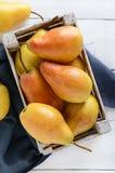 Peras amarillas jugosas grandes en una caja de madera rústica de la fruta en una tabla blanca Foto de archivo