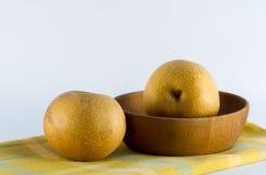 Peras asiáticas en el cuenco amarillo de madera de la servilleta de la tela escocesa Foto de archivo