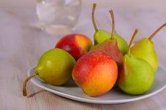 Peras com pêssegos em uma placa Fotografia de Stock Royalty Free