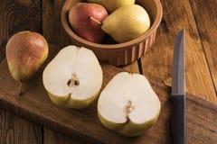 Peras cortadas em uma placa de madeira Imagens de Stock