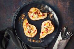 Peras cozidas com queijo azul e nozes, servidos com laranja e Imagens de Stock Royalty Free