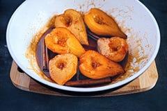 Peras doces caramelizadas no xarope de açúcar com varas de canela fotografia de stock