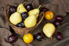 Peras e ameixas saborosos suculentas na cesta Fotografia de Stock