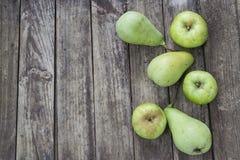 Peras e maçãs verdes com as folhas na tabela velha, de madeira ANG alto Foto de Stock