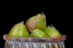 Peras em uma cesta isolada em um fundo preto Imagem de Stock