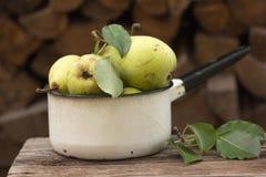peras en un pote del esmalte en un fondo natural de madera Imagen de archivo libre de regalías