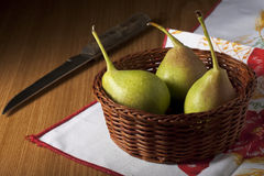 Peras en una cesta con el cuchillo Fotos de archivo