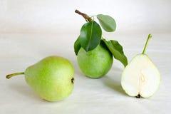Peras frescas con las hojas en un fondo ligero Todavía vida con las peras Fotografía de archivo