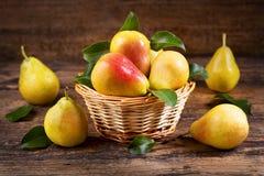 Peras frescas con las hojas en una cesta fotografía de archivo libre de regalías