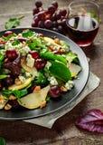 Peras frescas, ensalada del queso verde con la mezcla verde vegetal, nueces, uvas rojas Alimento sano Imágenes de archivo libres de regalías