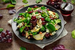 Peras frescas, ensalada del queso verde con la mezcla verde vegetal, nueces, uvas rojas Alimento sano Fotos de archivo