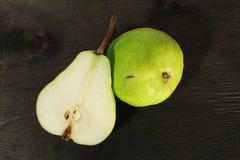 peras frescas no fundo de madeira preto Imagens de Stock