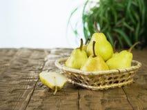 Peras maduras en una cesta en una tabla de madera rústica Foto de archivo