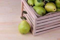 Peras maduras frescas en una caja de madera en un fondo de madera natural foto de archivo
