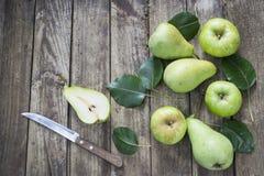 Peras, manzanas y cuchillo verdes con las hojas en la tabla vieja, de madera Imagen de archivo