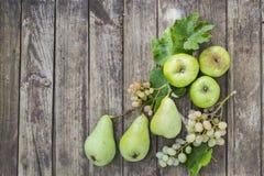 Peras, manzanas y uva verdes con las hojas en la tabla vieja, de madera Fotografía de archivo libre de regalías