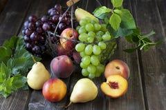 Peras, nectarinas, uva y melocotones deliciosos en una tabla de madera rústica Imágenes de archivo libres de regalías