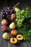Peras, nectarinas, uva y melocotones deliciosos en una tabla de madera rústica Imagen de archivo libre de regalías