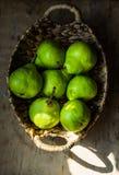 Peras orgânicas verdes maduras na cesta de vime do vintage na mesa de cozinha de madeira resistida, mancha da luz solar Fotografia de Stock Royalty Free