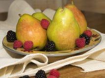 Peras verdes con las bayas maduras Imagen de archivo libre de regalías