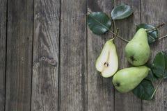 Peras verdes con las hojas en la tabla vieja, de madera Opinión de alto ángulo Imagen de archivo libre de regalías
