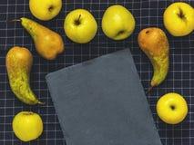 Peras verdes da conferência, maçãs verdes, uma ardósia da placa de corte em b Fotos de Stock