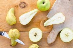 Peras verdes doces frescas com as maçãs na tabela de madeira Imagem de Stock