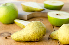 Peras verdes doces frescas com as maçãs na tabela de madeira Foto de Stock