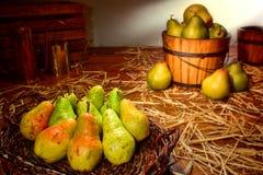 Peras verdes en cesta rústica en la granja del país viejo Imagen de archivo libre de regalías