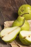 Peras verdes en un escritorio de madera rústico Imagen de archivo