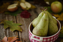 Peras verdes no prato cor-de-rosa com as maçãs no ajuste rústico Foto de Stock Royalty Free