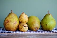 Peras verdes y amarillas en una toalla de cocina Fotografía de archivo libre de regalías