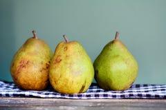 Peras verdes y amarillas en una toalla de cocina Foto de archivo libre de regalías