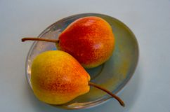 Peras vermelhas deliciosas bonitas em uma bandeja branca Imagens de Stock Royalty Free