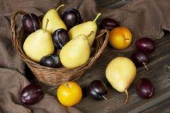 Peras y ciruelos saborosos jugosos en cesta Fotografía de archivo