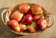 Peras y manzana rojas maduras en la cesta de la barra en la tabla de madera Fotos de archivo