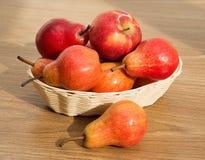 Peras y manzana rojas maduras en la cesta de la barra en la tabla de madera Fotos de archivo libres de regalías
