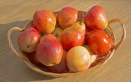 Peras y manzana rojas maduras en la cesta de la barra en la tabla de madera Fotografía de archivo libre de regalías